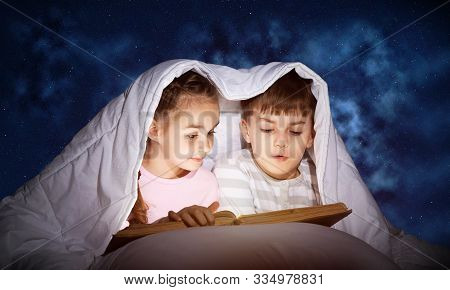 Engrossed Little Girl And Boy Reading Book In Bed After Bedtime. Pretty Kids Together Hiding Under B