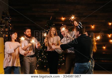 Cheerful Friends Are Dancing With Champagne Glasses And With Bengali Lights, Celebrating New Year. C