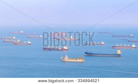 View Of Singapore Harbor With Many Cargo Ships At Sunset. Singapore