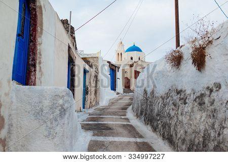Typical Street In Akrotiri Village On Santorini Island, Greece. White Houses With Blue Doors. Agia T