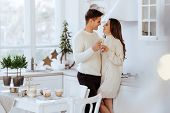 affectionate couple hugging in kitchen and looking at each other poster