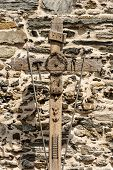 Old wooden cross with the symbols of the Passion of Christ, pincer, ladder, hammer, chalice, spear, crown of thorns, rooster, nails and text INRI. Vernazza village, Italy poster