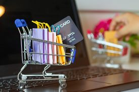Paper Shopping Bags And Mock-up Of Credit Card In Trolley On Laptop Keyboard. Consumer Can Buy Produ