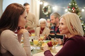 Young and mature women discussing something by served festive table during family dinner on Christmas eve