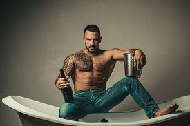 Handsome Bearded Shirtless Man In Jeans With Sexy Body In Bathroom. Sexual Macho Man In Bath. Strong