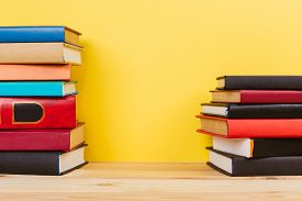 Simple Simple Composition Of Many Hardback Books, Unprocessed Books On A Wooden Table And A Yellow B