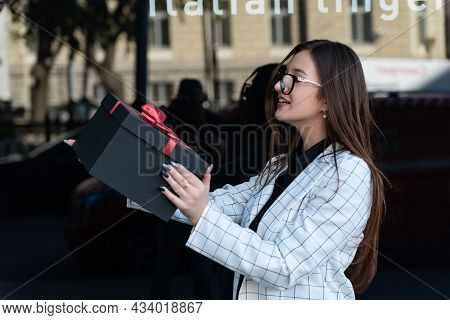 Young Cheerful Girl Holds Gift Box In Her Hands And Laughs. Happy Stylish Woman With Black Box In Ha