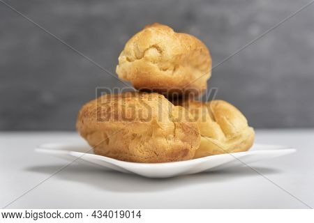 Delicate Profiteroles Or Eclairs Without Cream On Saucer. Gray Background