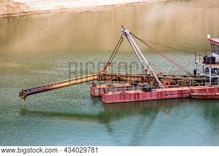 Front Part Of A Dredger With A Raised Suction Device On A Flooded Sandy Quarry
