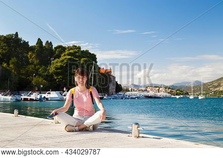 Smiling Young Female Tourist Sitting Cross-legged On Pier Holding Mobile Phone With Croatian Coastli