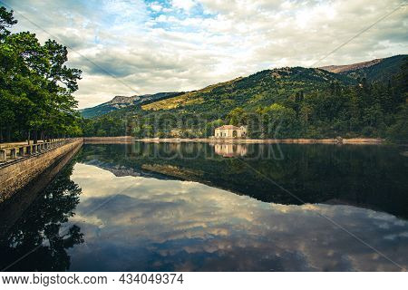 Reflection Of A House In The Lake, With Beautiful Views Of The Mountains That Are Also Reflected In