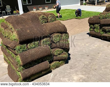 Rolls Of Fresh Sod Grass Piled On Wood Pallets For Installation At A New Home. Sod Is Also Being Pla