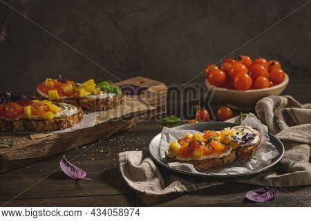 Italian Bruschettas With Roasted Tomatoes, Mozzarella Cheese, Pineapple Slices And Herbs On A Rustic