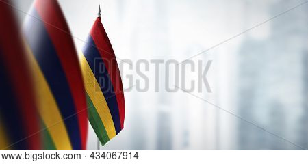 Small Flags Of Mauritius On A Blurry Background Of The City