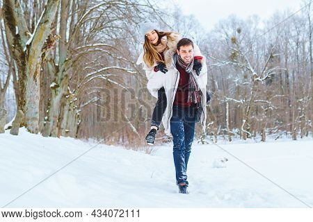 Happy Young Man Carry His Smiling Pretty Woman On His Back At Winter Park. Boyfriend Giving Piggybac
