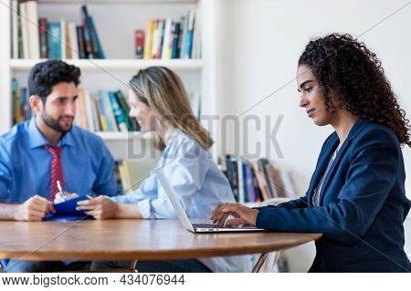 Hispanic Business Trainee Working At Computer With Colleagues At Office