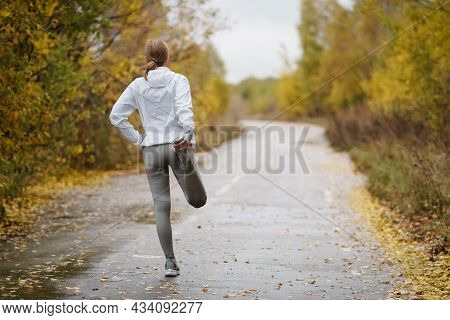 Athlete In The Autumn Park. Female Runner Stretching Before Running