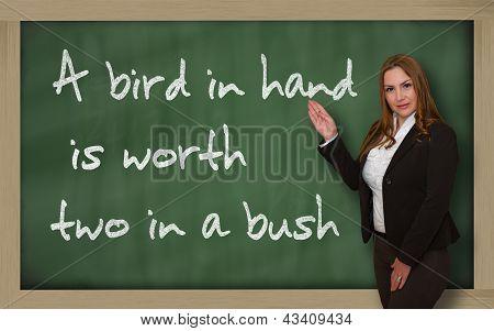 Teacher Showing A Bird In Hand Is Worth Two In A Bush On Blackboard