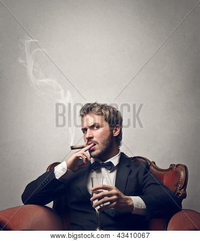 handsome boss smokes cigar sitting on a red armchair poster