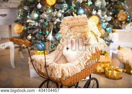 A White Rabbit Sits Inside A Retro Baby Stroller For Dolls. Christmas Vintage Decor, Christmas Tree