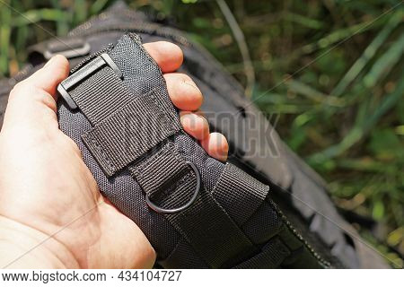 Hand Holds A Large Fabric Harness With A Metal Ring On The Tactical Backpack