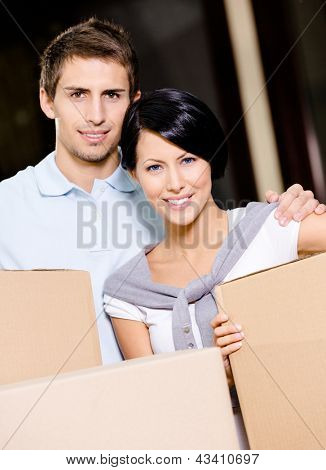 Married couple carrying cardboard boxes while moving to new house