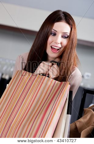 Woman doesn't want to let paper bags with gifts slip out of her hands