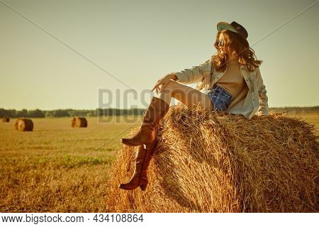 Summer and autumn fashion. Beautiful hippie girl sits on a haystack in a field and looks into the distance in the rays of the setting sun. Modern hippie and bohemian style. Copy space.