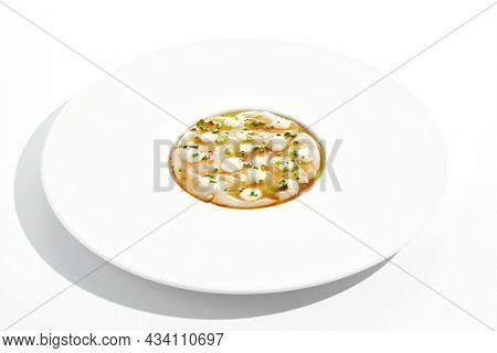 Delicious food - sea scallop carpaccio in yuzu sauce on white background. Scallop ceviche in japanese style. Scallop crudo in citrus sauce and creamy espuma. Delicacy seafood in restaurant menu