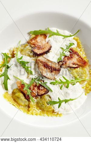 Mushroom ravioli and cheese sauce isolated on white background. Italian dish - ravioli with porcini and creamy espuma on white plate. Restaurant dishes with wild mushroom