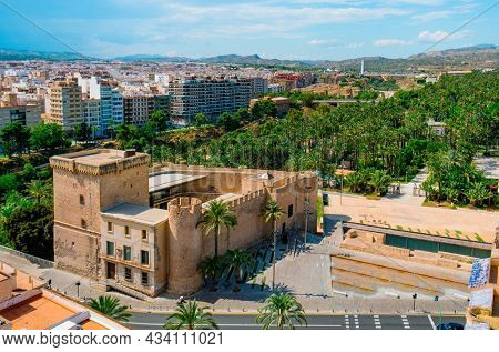 an aerial view of the Altamira Castle in Elche, Spain, and the famous Palmeral, known as Palm Grove of Elche in English, a public park with many palm trees