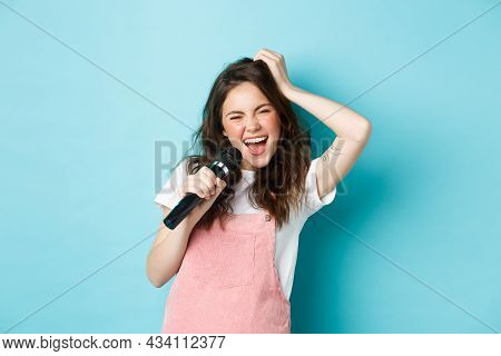 Beautiful Woman Singer Holding Microphone, Singing Karaoke In Mic, Standing Over Blue Background