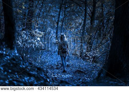 Creepy Woods At Night For Halloween, Girl Walking Alone In Mystic Dark Forest. Young Woman In Spooky