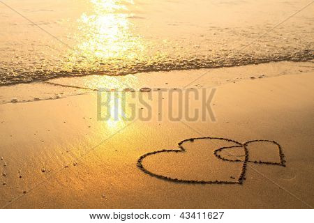 Hearts drawn on the sand of a beach, soft wave of the sea.