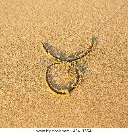 Zodiac sign Taurus, drawn on the facture beach sand. (zodiac signs series)