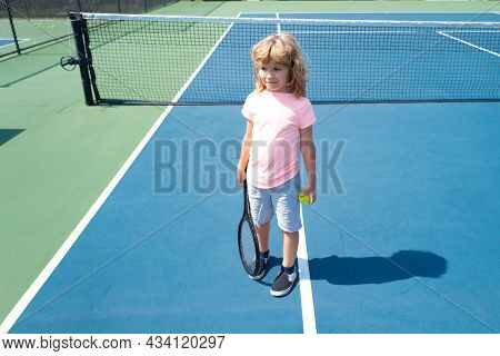 Child With Tennis Racket And Ball On Tennis Court Outdoor. Sport Exercise For Kids. Summer Activitie