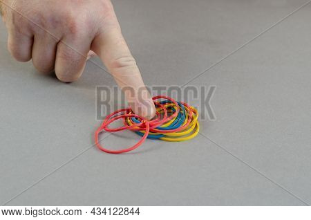 The Index Finger Points To The Rubber Bands. Groups Of Multicolored Round Rubber Bands On A Gray Bac
