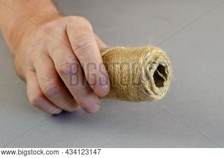 One Hand Holds A Coil Of Twine Against A Gray Background. A Man Shows The Thin Thread, Which Is Made