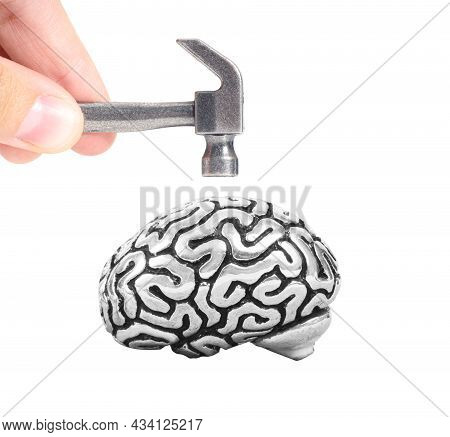 Crop View Of Male Fingers Holding A Small Steel Hammer Above A Metal Copy Of A Human Brain Isolated