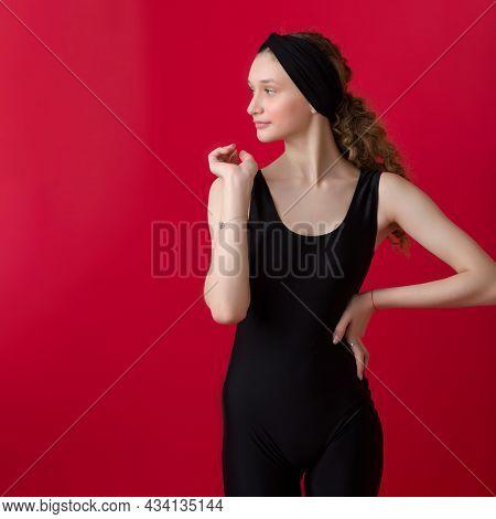 Beautiful Girl In Sportswear Posing In The Studio. Attractive Girl In Black Sportswear And Headband