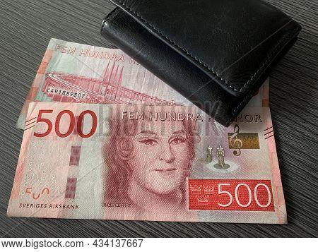 Sweden Krone Bills With Black Leather Wallet Isolated On Dark Wood Background. Swedish Krona Money -