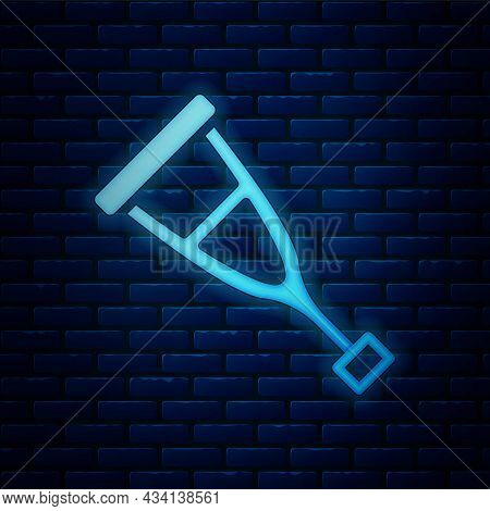 Glowing Neon Crutch Or Crutches Icon Isolated On Brick Wall Background. Equipment For Rehabilitation