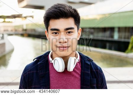 Portrait Of Handsome Young Asian Man With Headphones Standing Outdoors In City And Looking At Camera