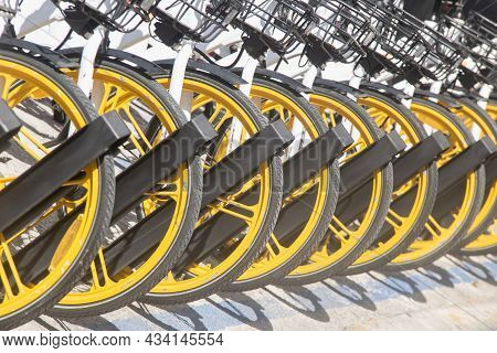 Close-up Of A Row Of Bicycles Parked. Row Of Parked Colorful Bicycles. Rental Yellow Bicycles.