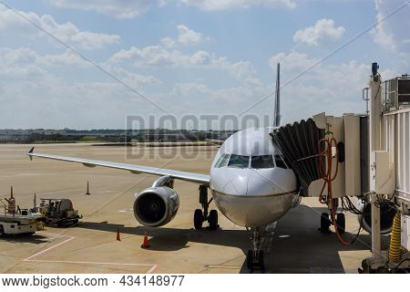 Jet Engine Against A Middle Size Plane At The Airport On Loading Aircraft At The International Airpo