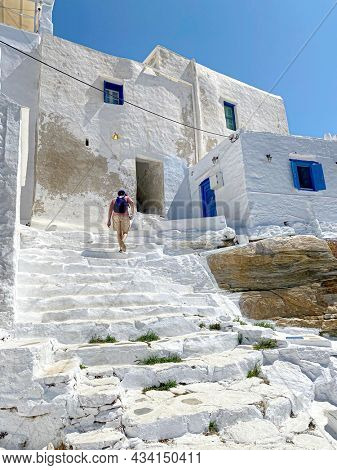 Unrecognisable male tourist, with backpack, exploring a greek village