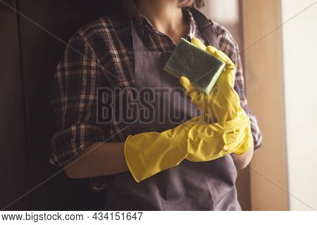 Young Female Hands In Yellow Rubber Gloves Hold A New Green Sponge For Cleaning House And Wiping Sur
