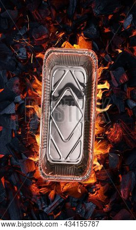 Empty aluminum foil food container on bbq grate over hot pieces of coals. Top view.