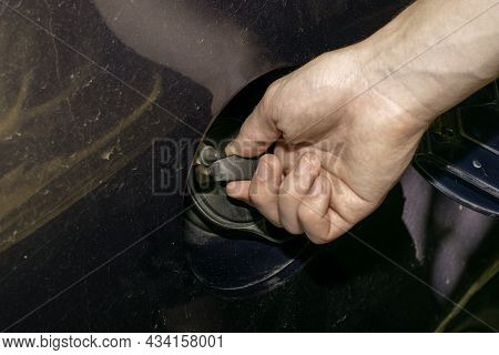 The Open Lid Of The Gas Tank Of An Old Car, A Person Unscrews The Neck Plug