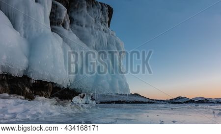 The Base Of The Rock Is Covered With A Layer Of Fancy Icicles, Similar To Frills. Fragments Of Ice A